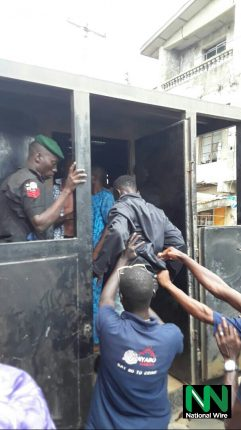 Police officers hauling a suspect into the Black Maria