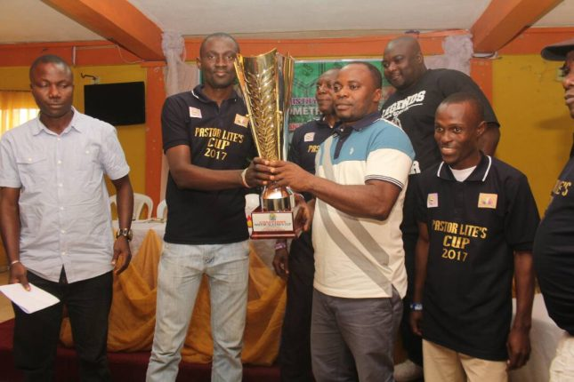 Mr. Segun Ajiroba presenting the trophy to Pastor Aromolaran while other organising team members watch