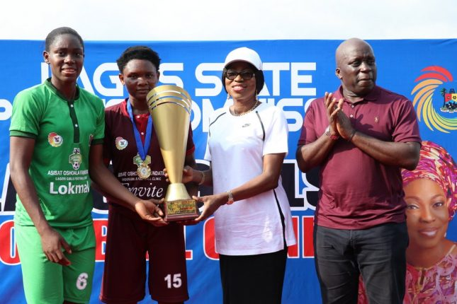 "Wife of the Governor of Lagos State, Mrs Bolanle Ambode (2nd right) supported by superstar footballer and super falcon, Asisat Oshoala (L); and SA to the Governor on Sports, Mr. Deji Tinubu, to present a trophy to the captain of the winning team, Lagos Team, after the exhibition match to mark the end of ""Lagos Girls' Football Clinic"" for secondary school girls, organized by Asisat Oshola Foundation, at Agege Stadium, Agege, on Friday, 17th November, 2017."